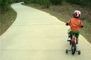little boy on bike with training wheels
